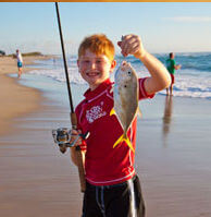 Young man hold up fish caught in Buxton NC National Seashore.