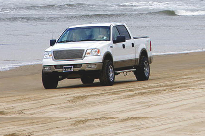 New Ford truck driving on beach at the Buxton NC NPS National Seashore.